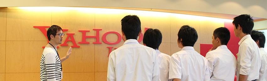社会貢献活動。壁面のYahoo! JAPANロゴを前に、会社見学の参加者に説明をするヤフー社員の写真。