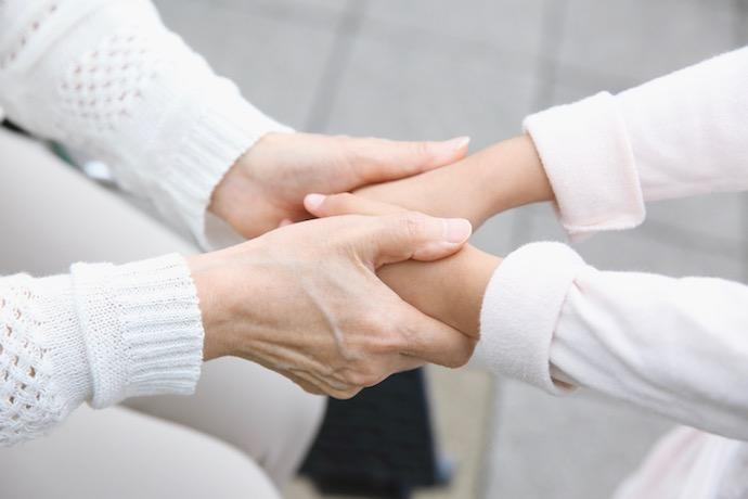 高齢者と手を取り合う。イメージ画像