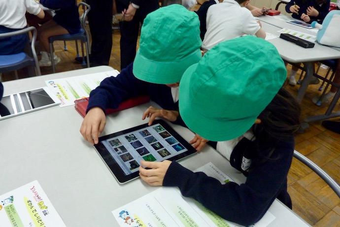 タブレットを使っている子供たちの写真