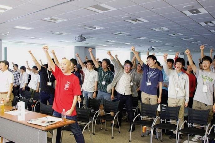 Hack Uの参加者が片手を挙げて全員で歓声を上げている様子の写真