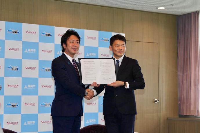 福岡市との包括連携協定締結にあたり福岡市長と宮坂社長が握手をしている写真