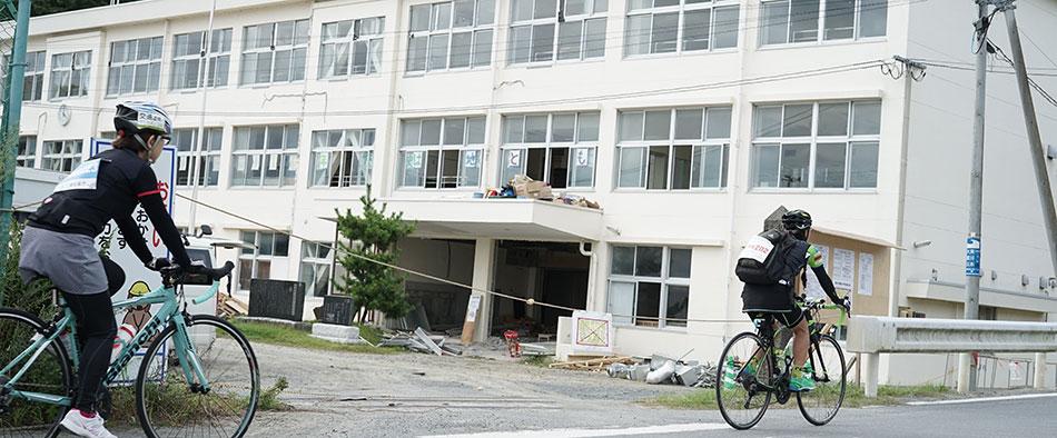 復興の手が入るのを待っている全壊状態の校舎前を走る