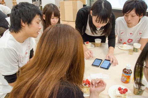 写真:サポーターズクラブのメンバーがスマートフォンの画面を囲みながら意見交換している様子