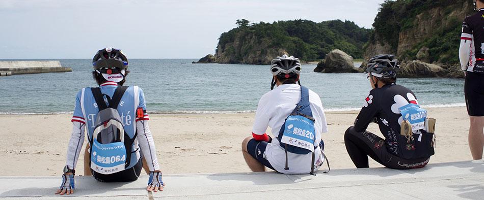 奥松島の月浜海水浴場に腰掛けて休憩するライダー