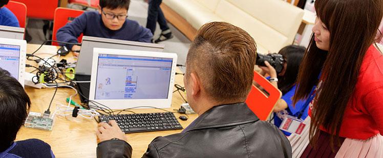 子供たちに混じってプログラミングに挑む田中の画像
