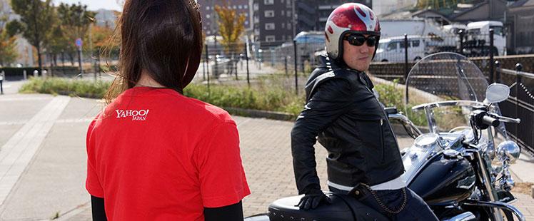 LIG田中がバイクに座りながらヤフー金澤に話しかけている様子