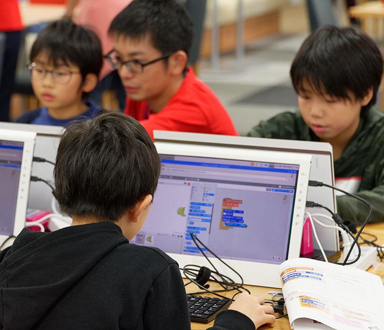 真剣な眼差しでプログラミングに取り組む子供たちの画像