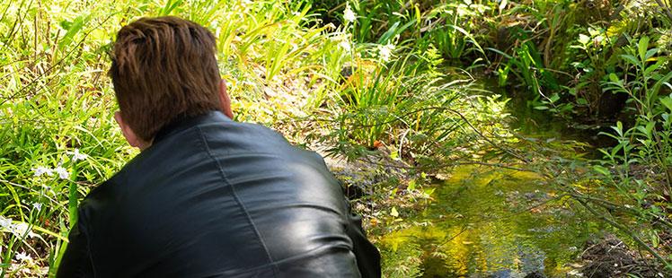ビオトープの小川の淵に座る田中の画像