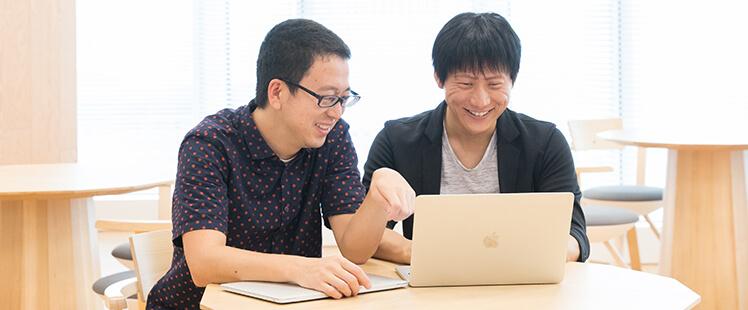 Yahoo! JAPAN研究所の坪内とヤフーのローカル検索開発部の丸山がパソコンを見ながら話している様子