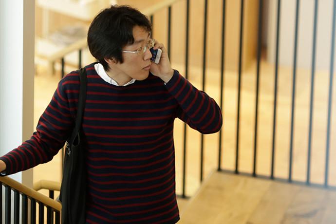 写真:階段でスマートフォンを片手に電話している 石切山 開