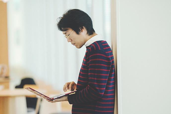 写真:オフィスでノートパソコンの画面をのぞき込んでいる 石切山 開