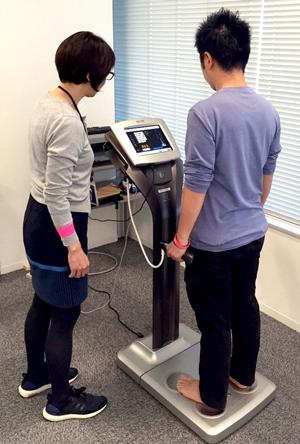 体組成計を利用し、体重・体脂肪・筋肉量などの測定を行っている様子