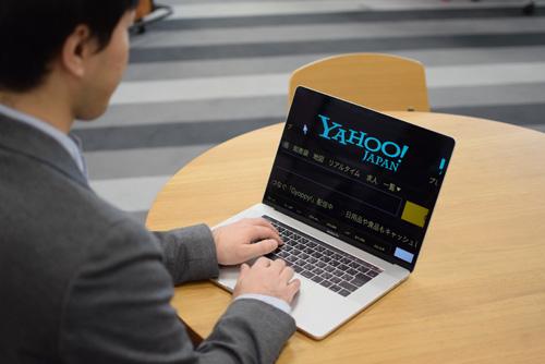 社員が画面を拡大できるパソコンを使っている写真