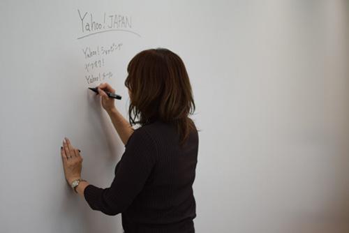 壁面ホワイトボードに文字を書いている社員の写真