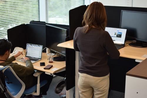 電動昇降デスクを使ってパソコンを使っている社員の写真