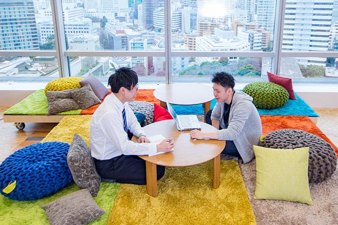社員食堂BASEの窓際のスペースで話し合う社員の写真
