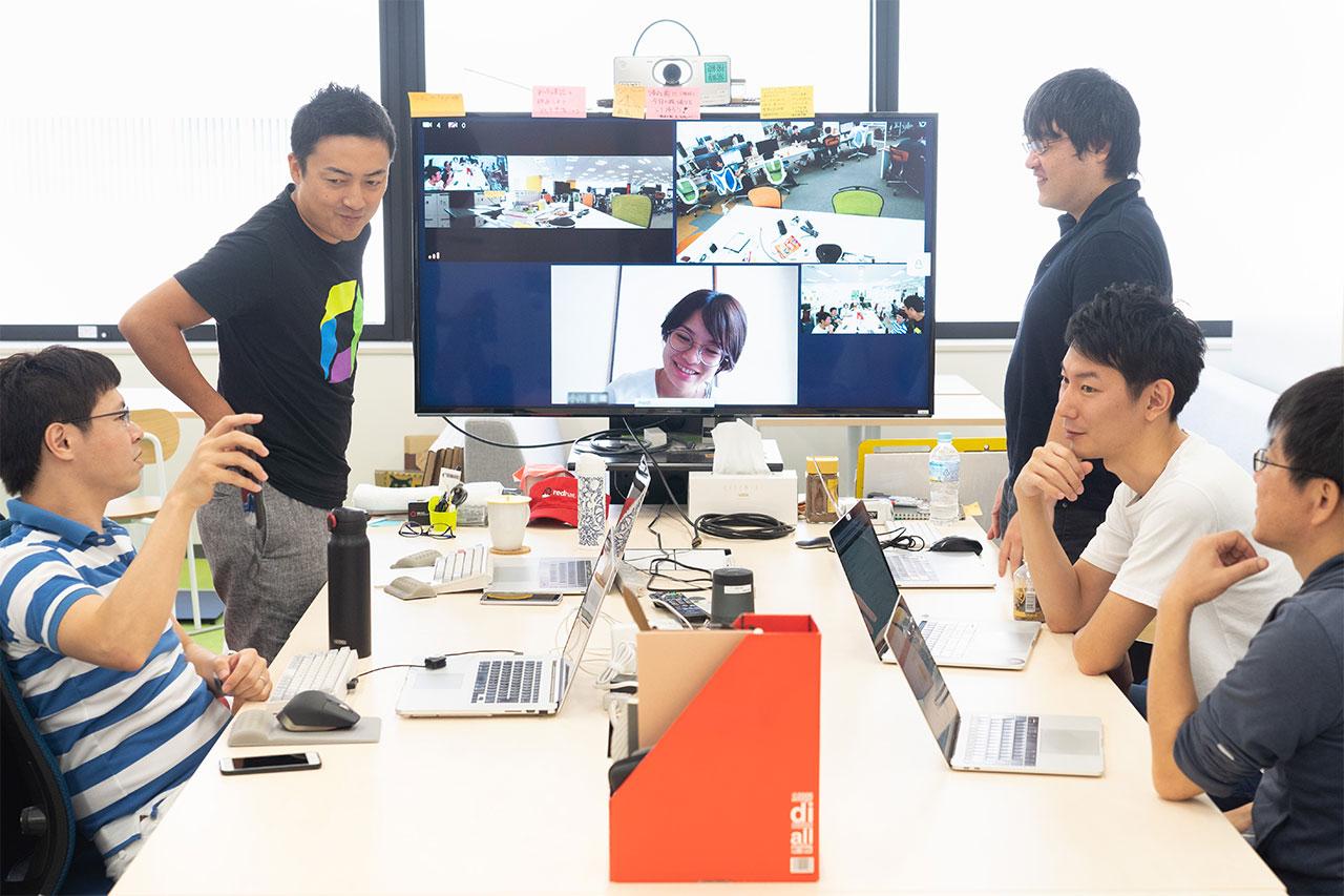 遠方のオフィスとテレビ会議をしながら議論を交わす社員たちの写真