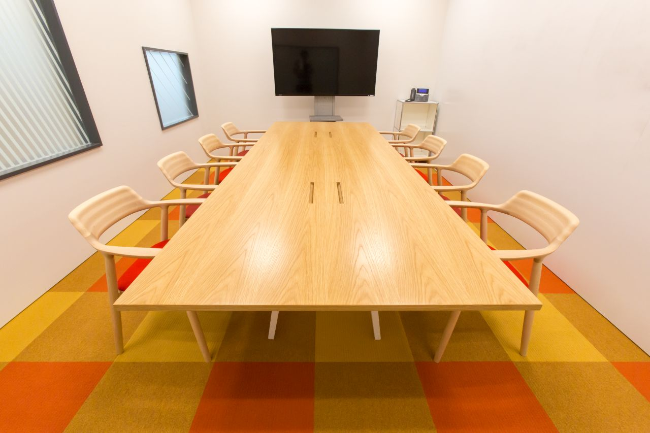 オレンジを基調とした来客用会議室の写真