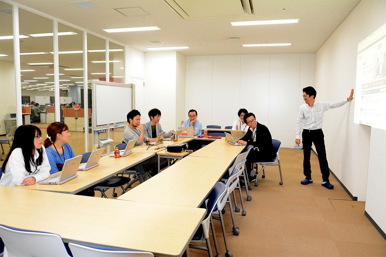 広い会議室で会議中の社員の写真