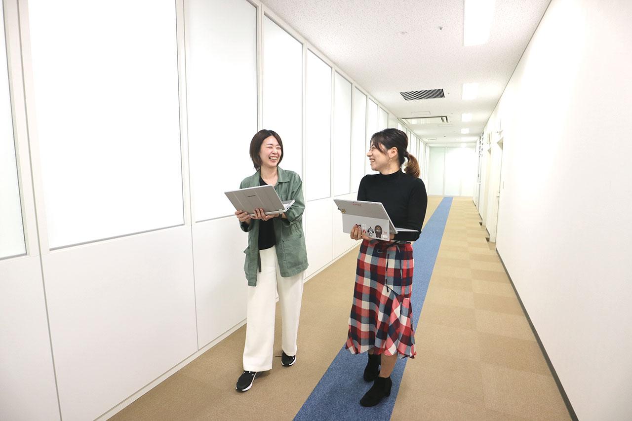 笑顔で会話しながら移動中の社員の写真