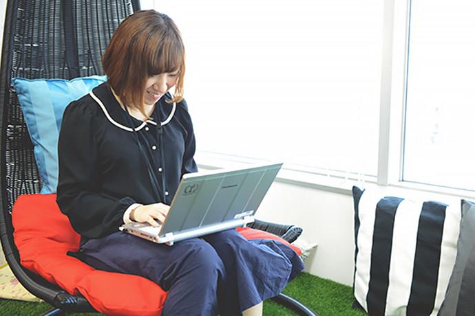 ハンモックチェアでパソコンを操作する社員の写真