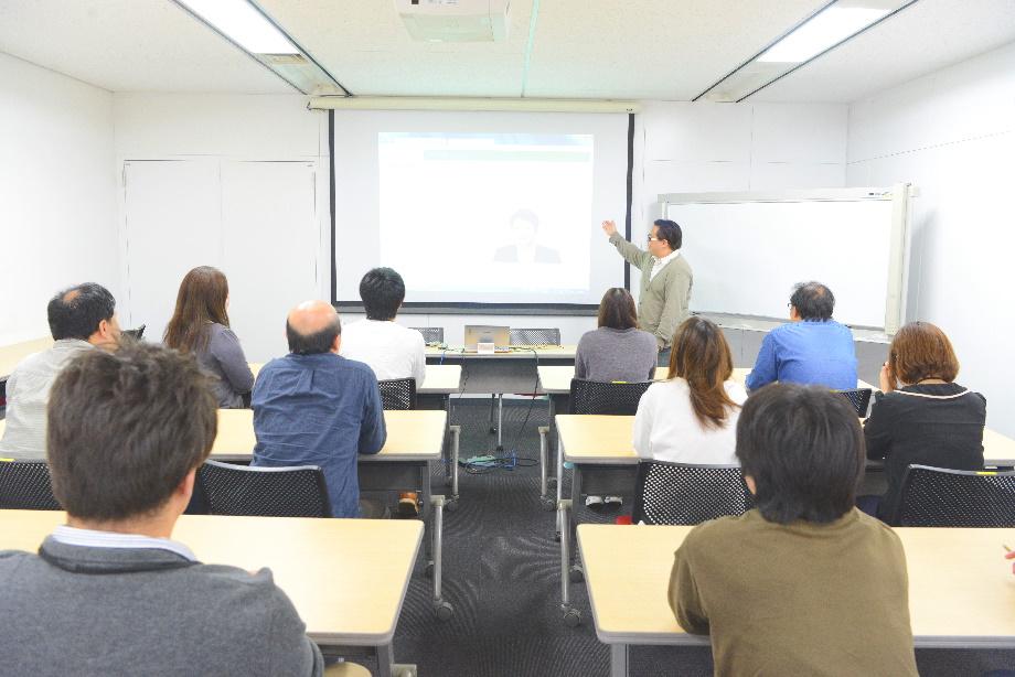 広めの会議室で投影されたスライドに目を向ける社員たちの写真