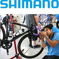 株式会社シマノのロゴと自転車のメンテナンスをしている写真