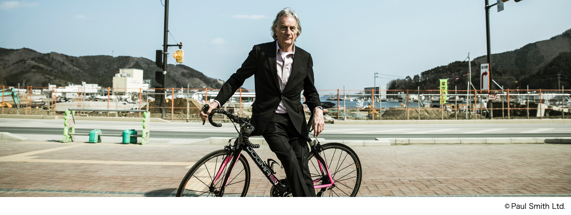 自転車にもたれかかるポール・スミス氏の写真