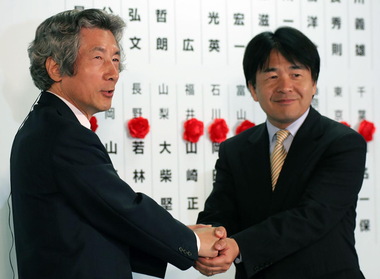 2004年7月の参院選で当選し、小泉元首相(左)と握手する竹中氏(写真:ロイター/アフロ)