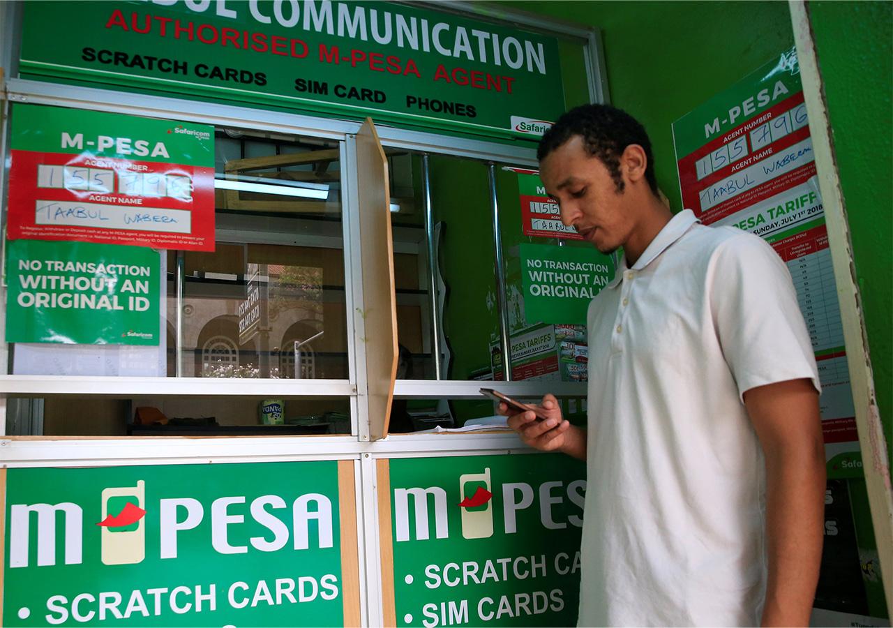 ケニアの首都ナイロビにあるM-PESA取扱店で送金する男性