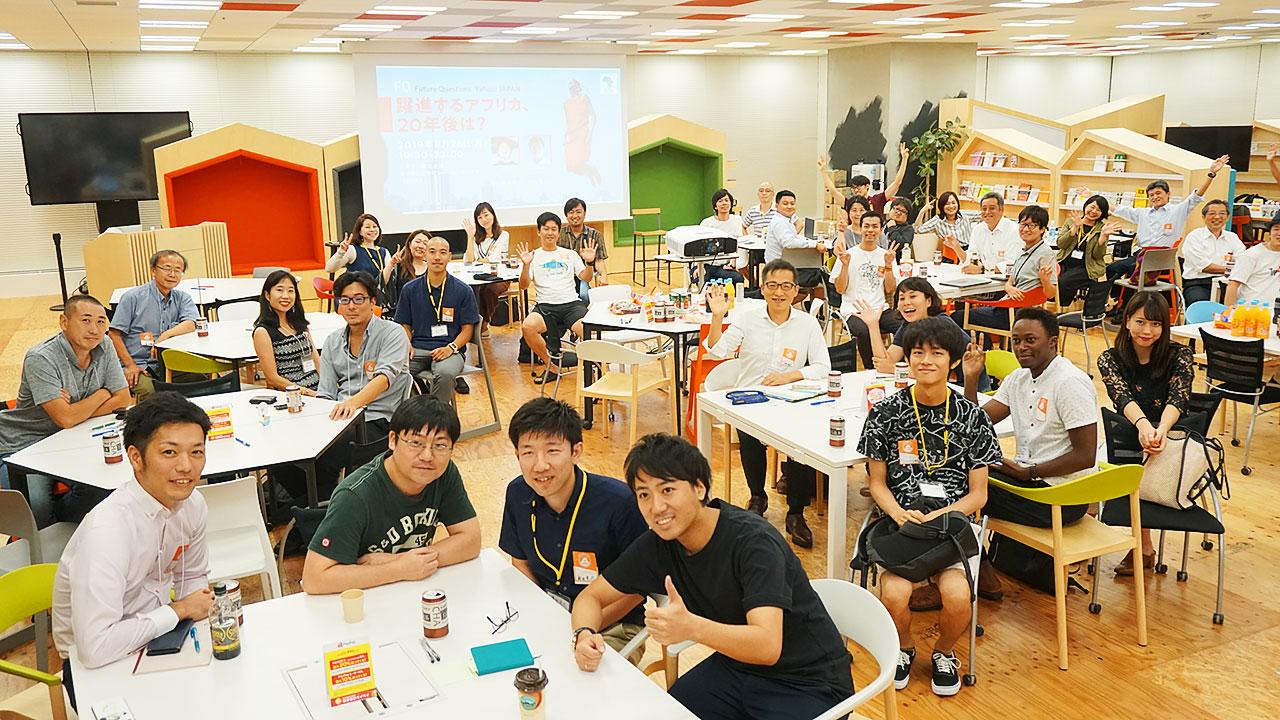 イベント参加者らに囲まれる寺久保さん(手前のテーブル右端)と合田さん(同右から3人目)