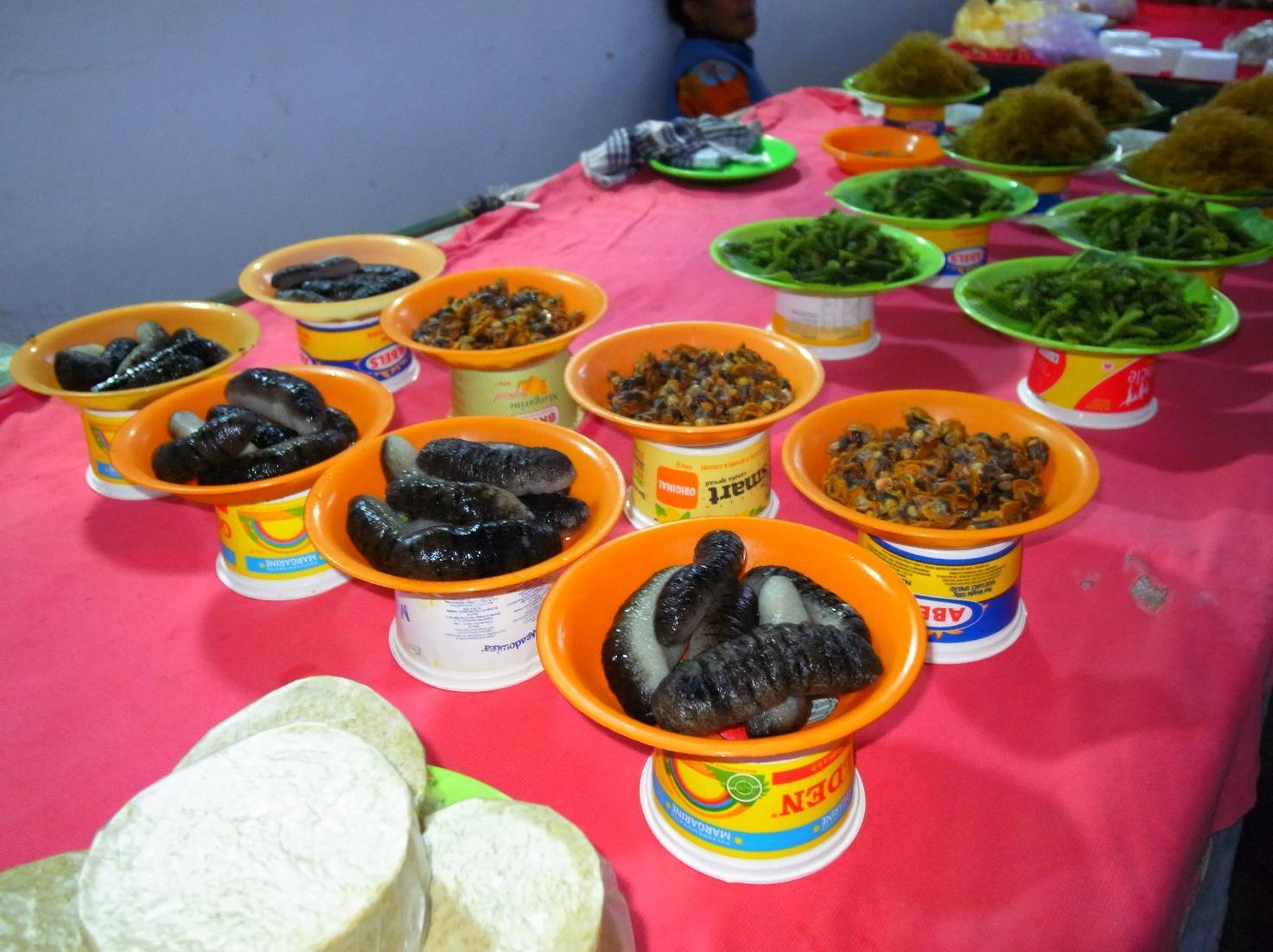 市場で販売される水産物、手前からナマコ、貝のむき身、海藻