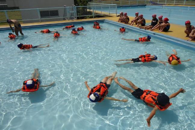 ライフジャケットをつけてプールに浮かぶ子ども達