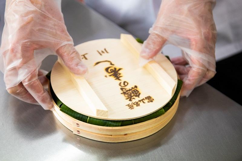 ます寿司を桶に詰める画像