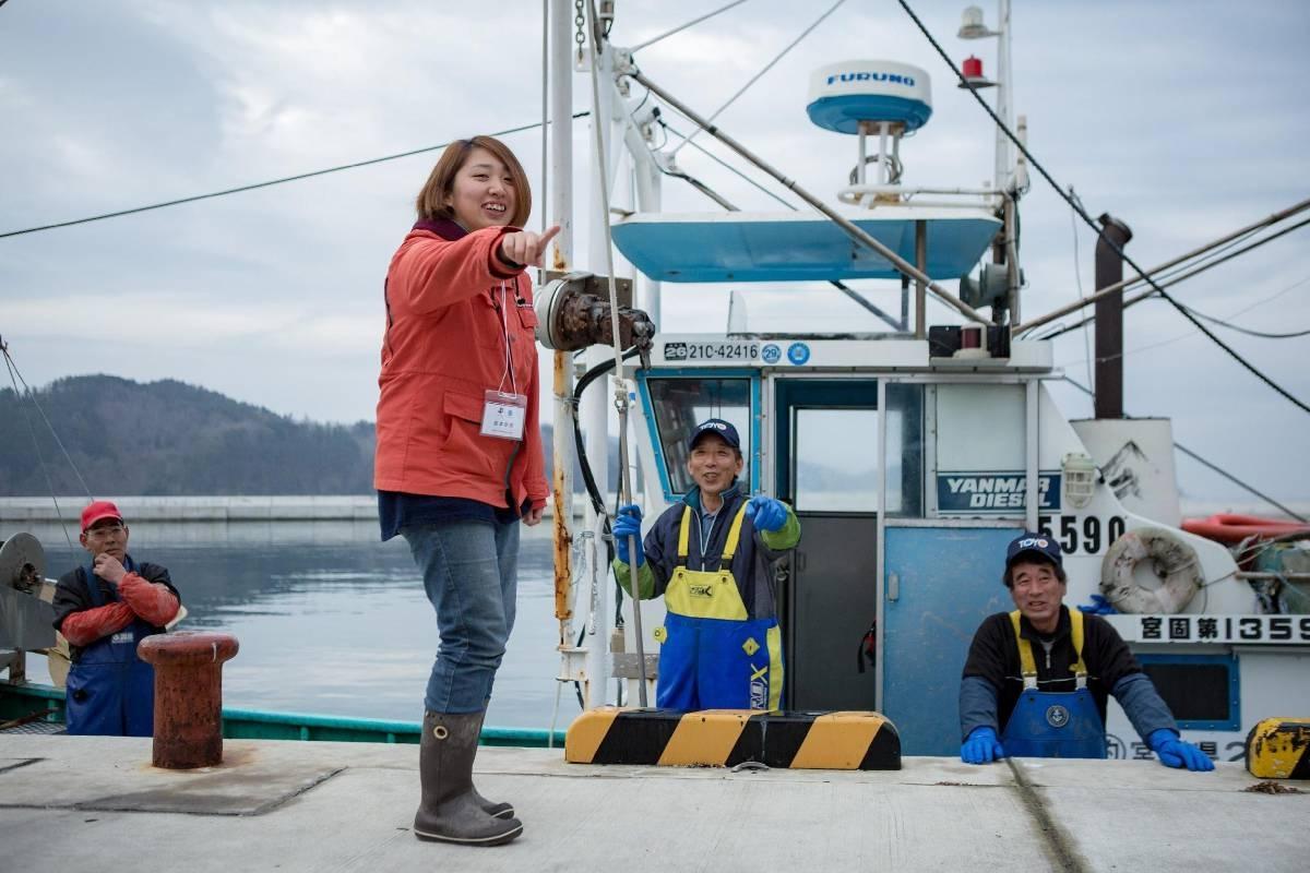 漁港で漁師と話す島本さん