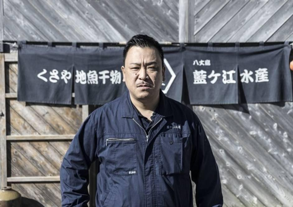 藍ヶ江水産の看板の前に立つ<b>加藤さん</b>