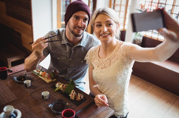 寿司と一緒に記念撮影する外国人旅行者