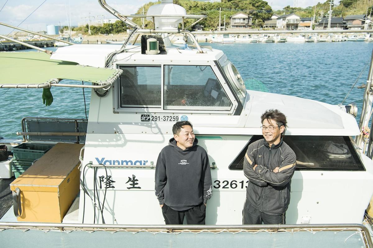 漁船でインタビューを受ける両羽さんと慎太郎さん