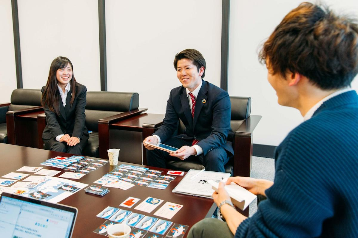 カードゲームの開発経緯について説明する田中さんと安藤さん
