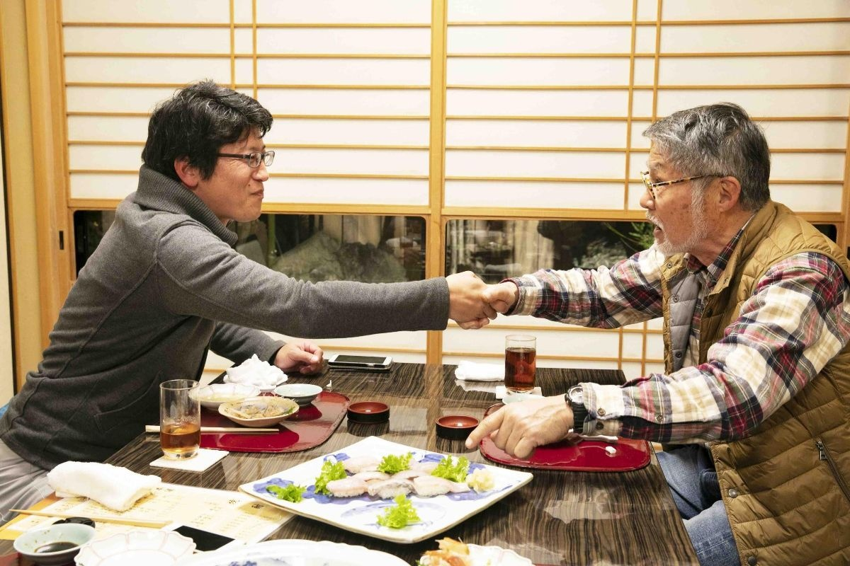 がっちりと握手する山崎さんと牧さん