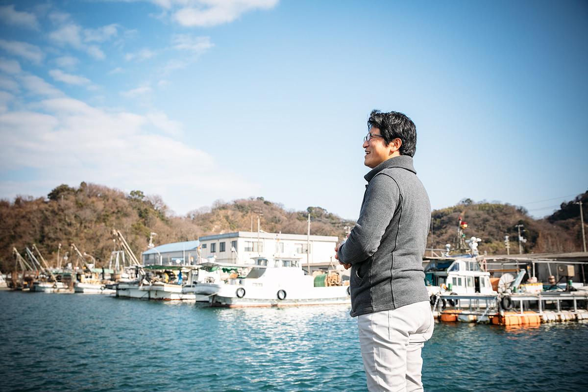 漁港で遠くを見つめる山崎さん