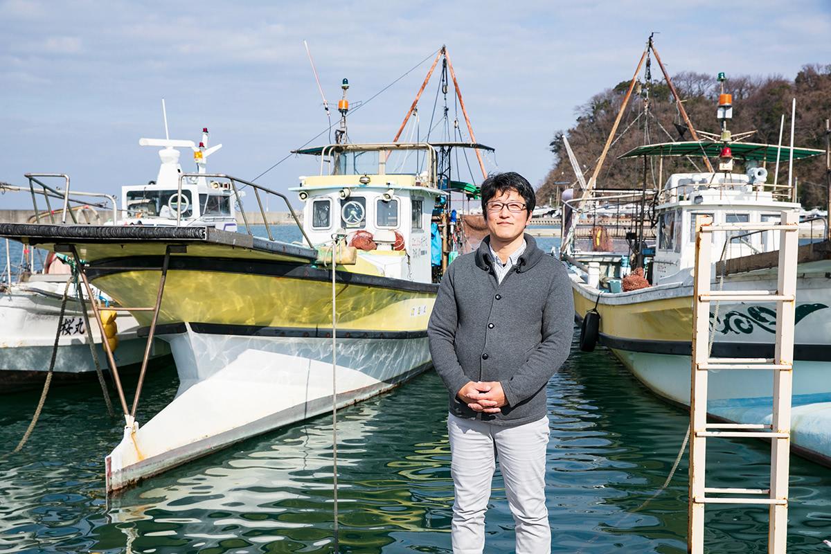 漁船の前に立つ、山崎さん