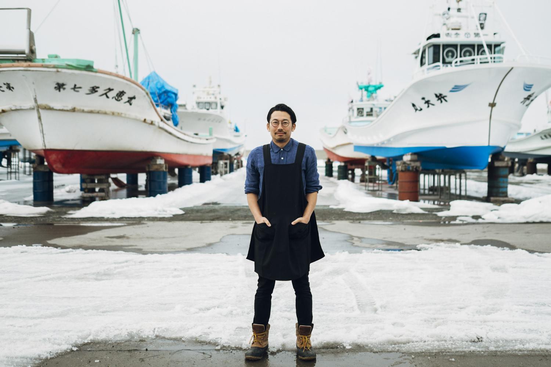 船を背景に立つ川口さん