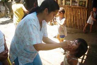 子どもにビタミンAを投与する看護師