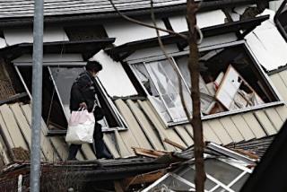 地震で倒壊した家屋から荷物を持ち出す住民=23日午前10時58分、長野県白馬村【提供:時事通信社】