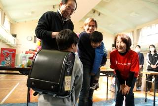 ランドセルを子どもに手渡す校長先生とスタッフ