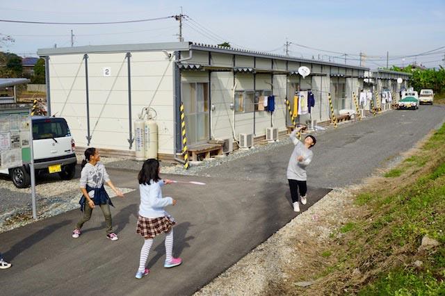 仮設住宅でバドミントンをして遊ぶ蘭愛さん(右)たち