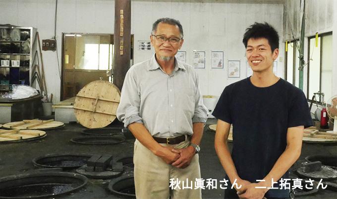 画像:工房で並んで微笑む秋山眞和さんと二上拓真さん