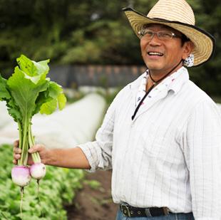 画像:カブを片手に微笑む山口雅行さん