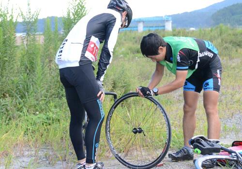 写真:参加ライダーの自転車のタイヤをチェックする走行管理ライダー